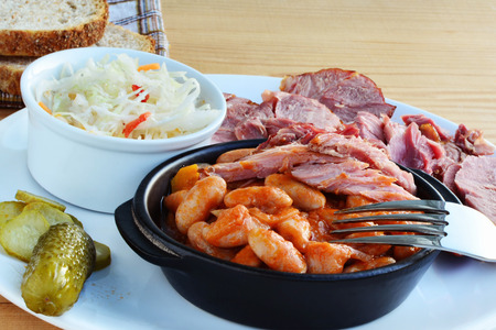 hock: Beans stew in tomato sauce with smoked ham hock meat pickles and coleslaw on plate.
