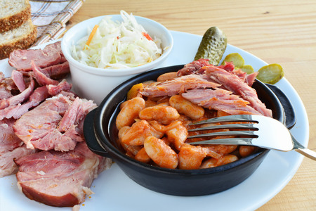 hock: Stewed beans in tomato sauce with smoked ham hock meat pickles and coleslaw on plate.