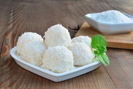 coco: Blancos de chocolate trufas de coco dulces en un plato en forma de corazón sobre la mesa de madera. Foto de archivo