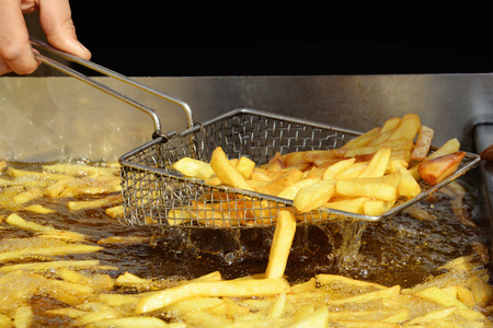 Delicious French fries are taken out from hot oil.
