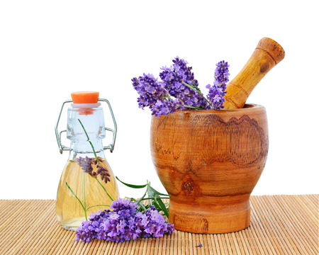Lavender essential oil with lavender flowers in wooden mortar.