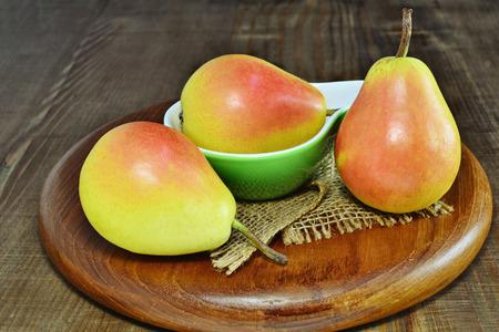 communis: Three ripe pears over wooden board. Santa Maria Pears (Pyrus communis)