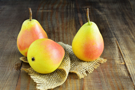 pyrus: Three ripe pears over wooden table. Santa Maria Pears (Pyrus communis)