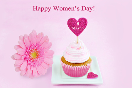 8 march: 8 March Womens Day pink greeting card with cupcake, heart and gerbera daisy. Stock Photo