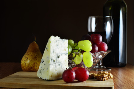 veined: Wedge of French blue veined cheese with grapes and red wine on wooden board. Stock Photo