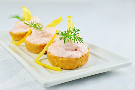 Taramasalata canape, fish-roe spread bites with lemon slices on white tray, Shallow dof.