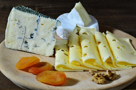 candied fruits: Cheese assortment, emmentaler, blue cheese, camembert with candied fruits on wooden board.