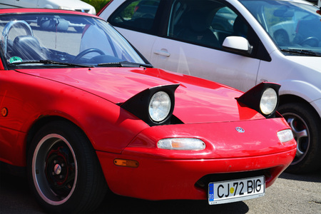 roadster: CLUJ-NAPOCA, ROMANIA - APRIL 16, 2016: Classic red Mazda MX-5 NA Series I (Mazda Miata), two-seat convertible roadster with retractable headlamps at the 2016 Retro Spring Parade. Editorial
