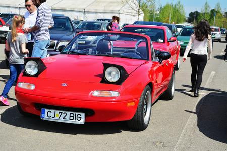 retractable: CLUJ-NAPOCA, ROMANIA - APRIL 16, 2016: Classic red Mazda MX-5 NA Series I (Mazda Miata), two-seat convertible roadster with retractable headlamps at the 2016 Retro Spring Parade. Editorial