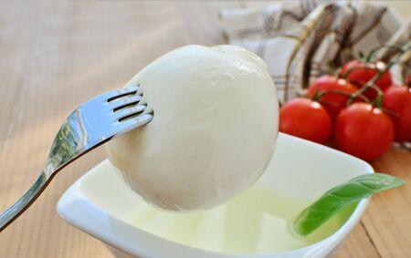 brine: Mozzarella cheese ball on fork brine in bowl