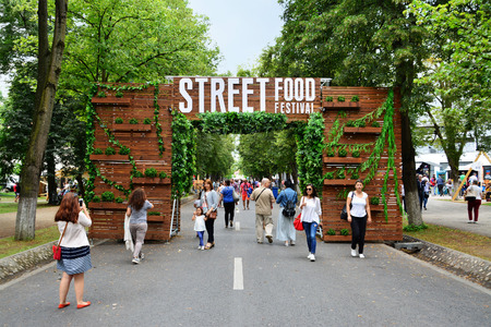 CLUJ-NAPOCA, ROMANIA - JULY 9, 2016: Decorated wooden gate welcomes visitors to the outdoor street food festival in central park Cluj. Редакционное