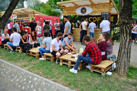 stalls: CLUJ-NAPOCA, ROMANIA - JULY 9, 2016: People have a snack at the Street Food Festival in central park Cluj. Vendors in stalls sell tasty fast food from different cultures.