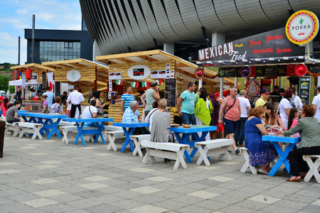 CLUJ-NAPOCA, ROMANIA - JULY 9, 2016: People have a snack at the Street Food Festival in front of the Cluj Arena stadium in central park Cluj. Vendors in stalls sell fast food from different cultures.