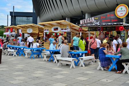 Cluj-Napoca, Rumunia - 09 lipiec 2016: Ludzie mają przekąskę Street Food Festival naprzeciwko stadionu Cluj Arena w Central Parku Cluj. Sprzedawcy w straganach sprzedają fast food z różnych kultur. Publikacyjne