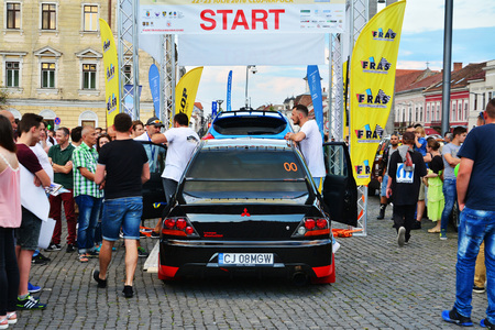 admire: CLUJ-NAPOCA, ROMANIA - JULY 21, 2016: People admire the race cars aligned at start at the Transilvania Rally 2016 opening ceremony in Cluj-Napoca Editorial