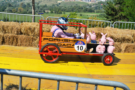 CLUJ-NAPOCA, ROMANIA - SEPTEMBER 3, 2016: unidentified racer drives a diy racecar with toy pigs down the racetrack at the Red Bull Soapbox Race Stock Photo - 62167624