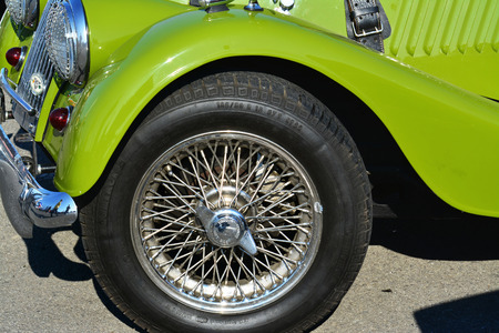 CLUJ-NAPOCA, ROMANIA - SEPTEMBER 24, 2016: Wire-spoked wheel of a vintage Morgan Plus 4 roadster classic car parked in the parking lot. Editorial