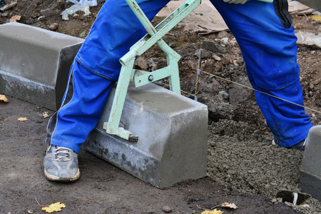 kerb: Worker lifts concrete curb with a manual lifting tool. Concrete kerb installation at sidewalk edging. Stock Photo