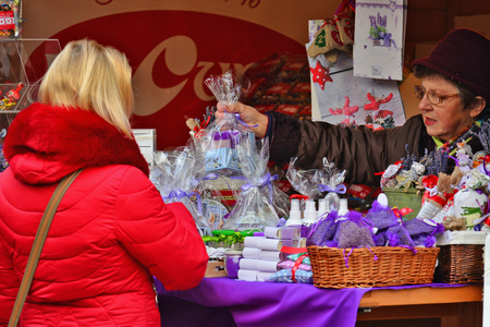 over packed: CLUJ-NAPOCA, ROMANIA - DECEMBER 17, 2016: Vendor hands over a gift package to buyer at the market. Blond woman shops cosmetics packed in cellophane