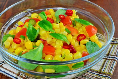 Fresh vegetable salad with corn, lambs lettuce, chilly, sweet pepper and tomatoes Stock Photo