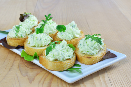 Herded cream cheese with rucola canapes on white plate