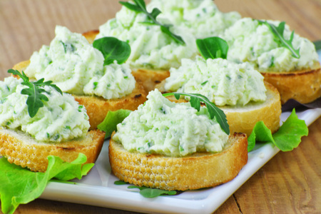 Cream cheese bites with rucola and herbs. Savory party canapes on white plate.