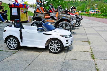 CLUJ-NAPOCA, ROMANIA - JUNE 3, 2016: Electric toy cars for kids to rent. Kiddie ride in the park. Editorial