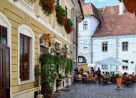 CLUJ-NAPOCA, ROMANIA - AUGUST 4, 2012: Tourists visit and have lunch at outdoor restaurant cafe outdoors in the old historic town center in front of the Matthias Corvinus Memorial House.