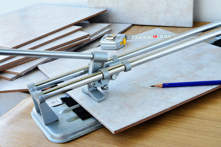 Cutting ceramic tiles with manual tile cutter machine, DIY home remodeling.