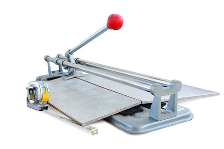 Tile cutter tool cutting a ceramic tile, isolated on white.   Stock Photo