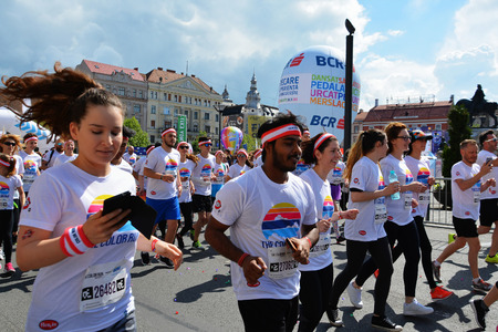 CLUJ-NAPOCA, ROMANIA - May 14, 2017: Color Run participants of all ages and genders wearing colorful t-shirts and headbands take off from the starting line as the race begins. Editorial