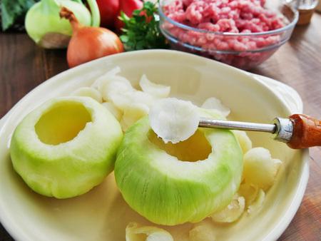Scooping out tender kohlrabi interior. Cooking stuffed kohlrabi Stock Photo