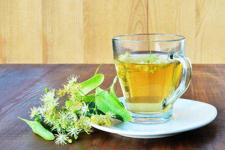 lime blossom: Cup of linden tea in glass mug over wooden table Stock Photo