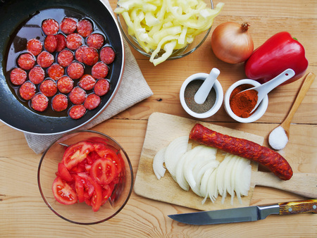 Vegetable stew ingredients. Cooking lecho with sausage, vegetables and spices on wooden table