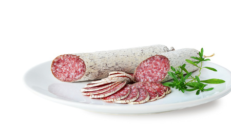 hungarian: Winter salami sticks and slices on white plate isolated on white background