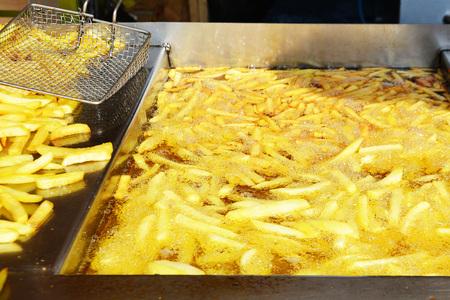 Frites françaises bouillant dans de l'huile chaude Banque d'images
