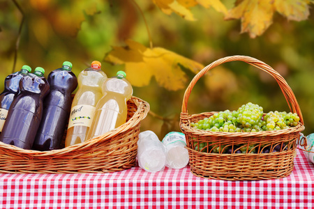 Freshly pressed must, grape juice or young wine in bottles near a basket of grapes on a table.