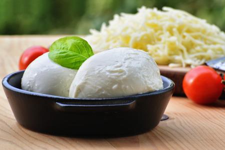 Mozzarella-Käsebällchen in Schale und geriebener Mozzarella mit Kirschtomaten Standard-Bild - 87398140