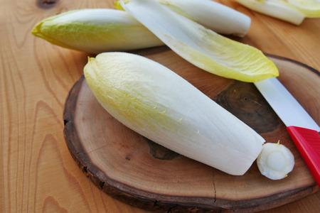 Belgische Endivie, rohes Gemüse der Zichorie oder witloof auf hölzernem Brett - Chichorium intybus Standard-Bild - 87648313
