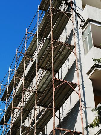 Wohnblock, der Außensanierungsarbeiten erfährt. Metallgerüst wird nahe Gebäudewand angehoben. Standard-Bild - 87700948