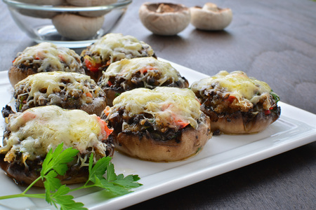 portobello: Stuffed mushrooms with cheese, bacon and vegetables on white serving plate