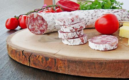 Wurstsalami mit der weißen Form und Käse geschnitten auf wooen Brett mit Tomatennahaufnahme Standard-Bild - 87849408