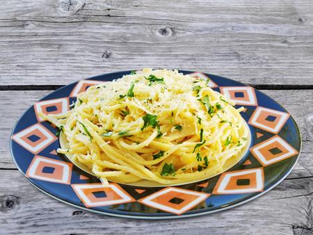 Spaghetti mit Käse und Kräutern in bunten Teller auf Holztisch Standard-Bild - 88033498