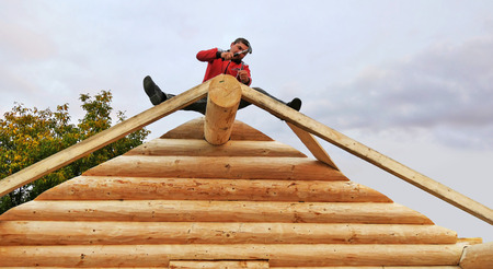 CLUJ-NAPOCA, ROMANIA - OCTOBER 13, 2017: Log cabin building. Carpenter driving nails with framing hammer, fixing square timber rafters for roof structure.