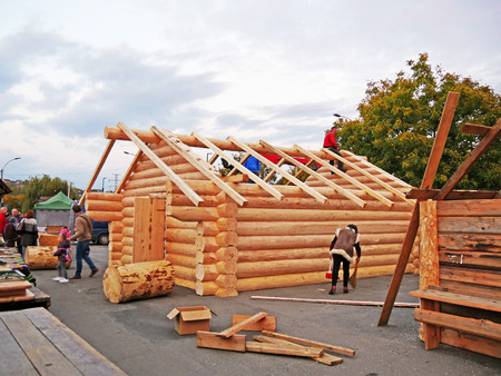 CLUJ-NAPOCA, ROMANIA - OCTOBER 13, 2017: Log cabin building in progress. Carpenters assemble timber  frame with common rafters on cabin roof. worjing on the cabin roof structure assembling square timber raftersCarpenters lifting square timber rafters to t Standard-Bild - 87506969