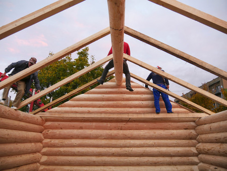 CLUJ-NAPOCA, ROMANIA - OCTOBER 13, 2017: New log cabin interior. Carpenters assemble timber  frame with common rafters on cabin roof in the evening Standard-Bild - 87506970