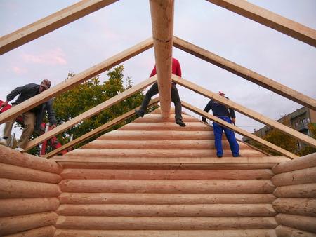 CLUJ-NAPOCA, RUMÄNIEN - 13. OKTOBER 2017: Neuer Blockhausinnenraum. Tischler montieren am Abend Holzrahmen mit gemeinsamen Dachsparren auf dem Kabinendach Standard-Bild - 87506970
