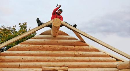 CLUJ-NAPOCA, RUMÄNIEN - 13. OKTOBER 2017: Blockhausgebäude. Tischler, der Nägel mit dem Gestaltungshammer, quadratische Bauholzsparren für Dachstruktur reparierend fährt. Standard-Bild - 87506971