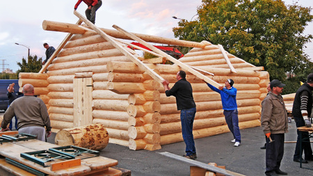 CLUJ-NAPOCA, ROMANIA - OCTOBER 13, 2017: Log cabin building. Carpenters lifting square timber rafters to the roof building timber frame structure for log cabin. Editorial