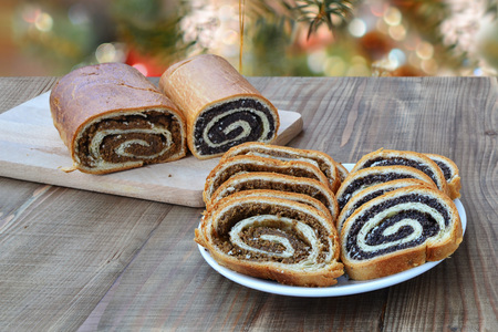 Poppy seed and walnut rolls, traditional Chistmas beigli cake on wooden table.